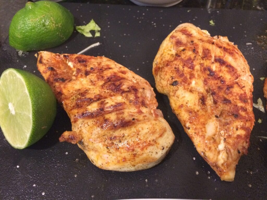 two grilled chicken breasts with sliced lime