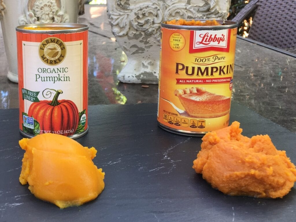 two cans of pumpkin puree with their contents scooped out