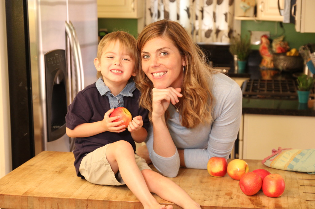 a woman and a child sitting on a counter holding an apple
