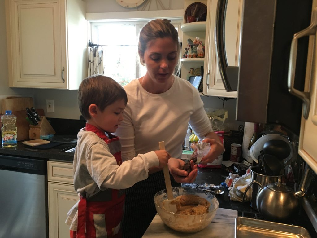 a woman and a child mixing a batter