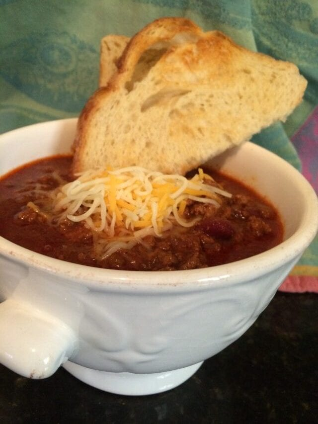 a bowl of Beef chili with a slice of toasted bread