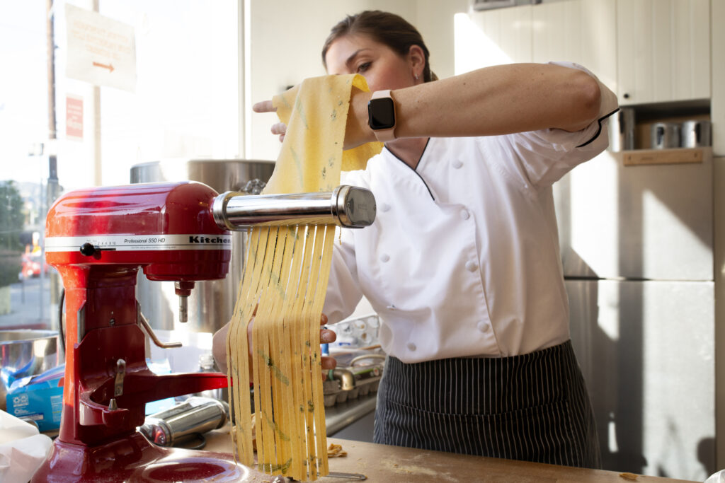 a woman making noodles from scratch using a machine