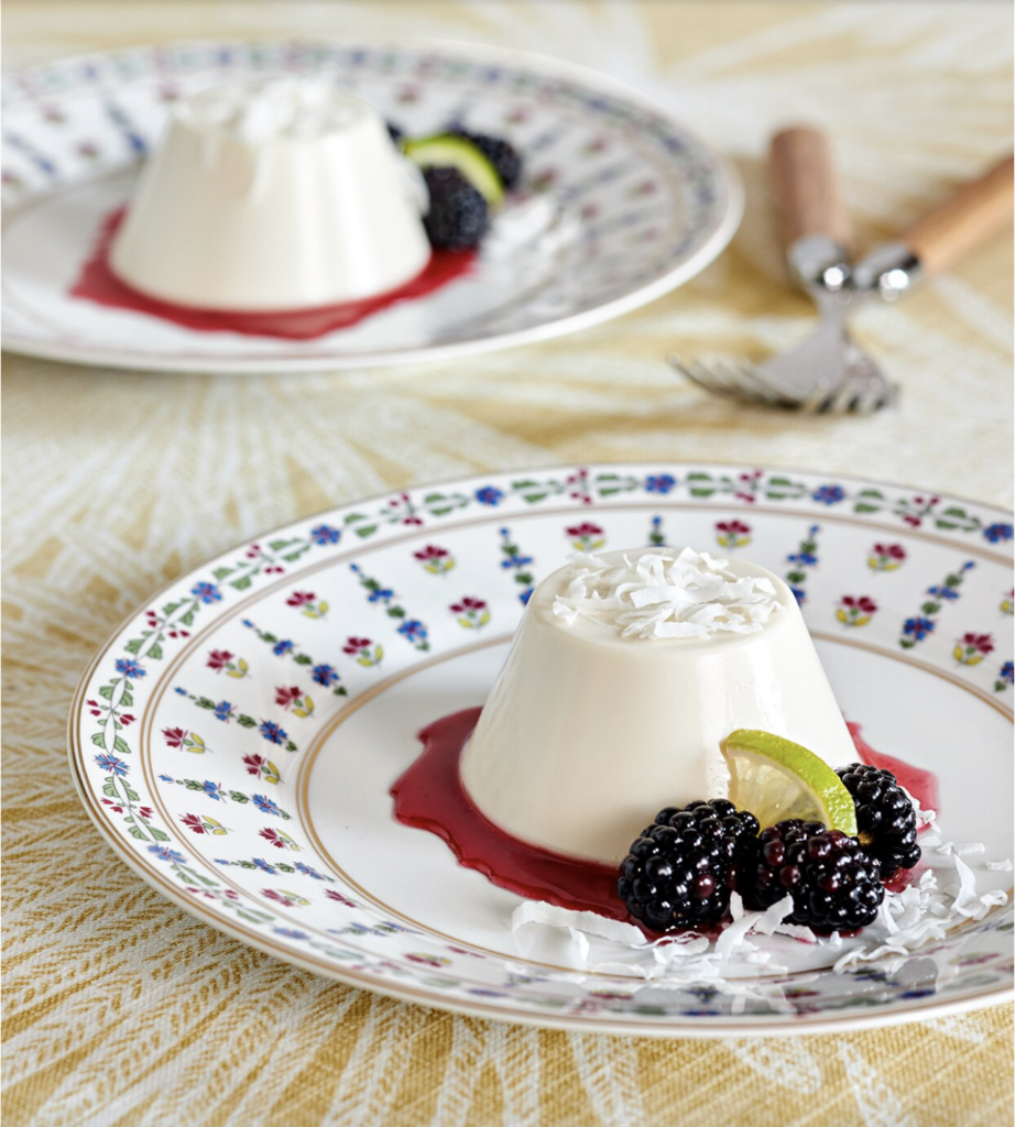 two Coconut Panna Cotta with Blackberry Sauce on plates